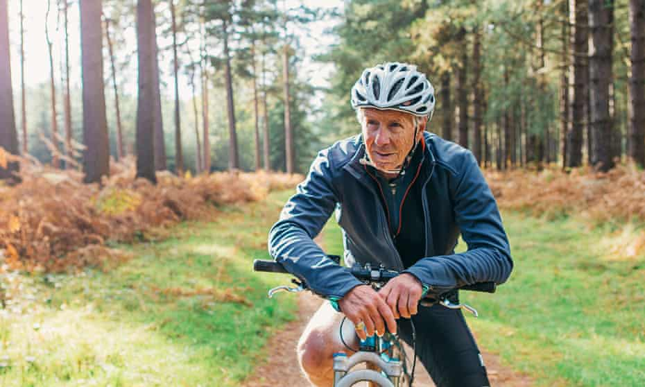 senior man on a bike in a forest