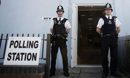 Police officers keep a watchful eye outside a polling station.