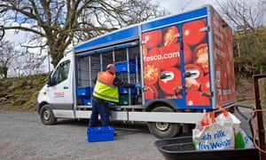 Tesco supermarket food van driver grocery delivery in plastic bags to a customer's home during the Covid-19 pandemic.