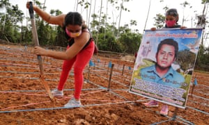 A protester at the site of a common grave for coronavirus victims in Peru demands proper burial for her relative.