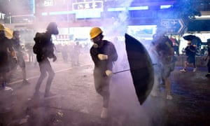 Protesters try to avoid tear gas let off by police.
