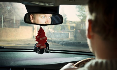 Stuart Heritage looking terrified in the reflection of the rear view mirror and the back of his head, a blurred view through the windscreen of the car he's driving