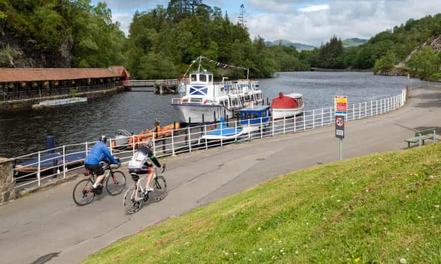 Trossachs Pier, Loch Katrine, Scotland, UK - cyclists passing the Lady of the Lake cruise boat