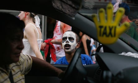 A boy dressed as a zombie gestures at a taxi driver