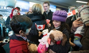 Syrian refugees Rezan Kurdi, left, and his sister Ranim Kurdi laugh after their family arrived at Vancouver international airport in December 2015.