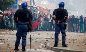 South African police face off the disgruntled residents angered at the lack of policing in the impoverished area
