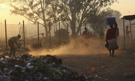 A man sweeps a path near a dumpsite in Harare