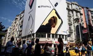 People cross the street underneath a billboard advertising the Apple iPhone X in Istanbul