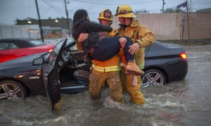 A firefighter carries a woman from her car after it was caught in street flooding.
