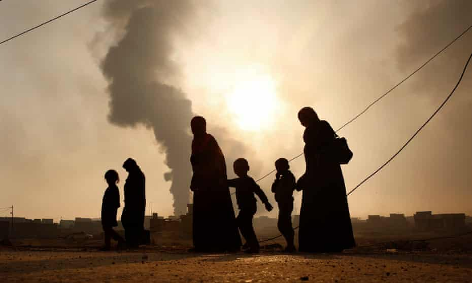 A family walks away from the front line in Mosul, Iraq