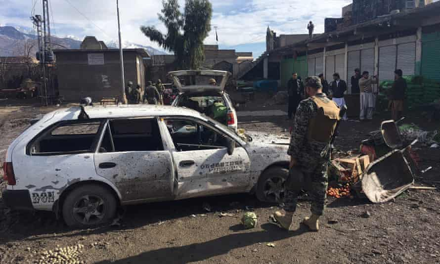 Pakistani security officals inspect the bomb explosion site at a vegetable market in Parachinar.