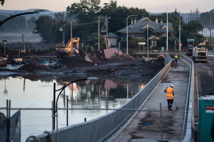 Workers clear debris on Saturday from the new Windsor Bridge, which was under water during the recent floods.