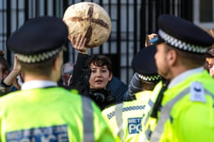 Members of the Extinction Rebellion climate activist group hold up loaves of bread in a protest outside Downing Street in London, UK