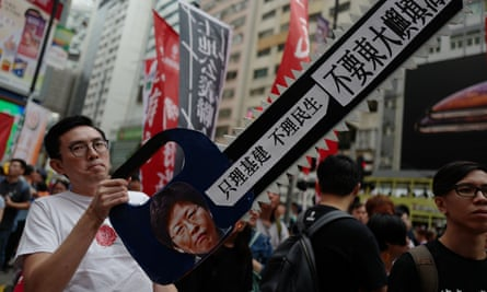 A protester holds a sign in the shape of a chainsaw with an image of Hong Kong chief executive Carrie Lam during a land reclamation protest in Hong Kong on Sunday.