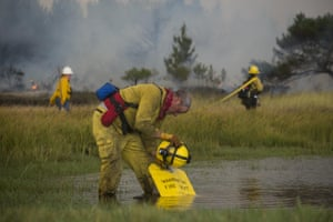 <strong>Warrenton, Oregon, US</strong> A firefighter uses a helmet to refill a water bag from a small pond while fighting a fire near the South Jetty at Fort Stevens State Park. Due to the location of the fire, trucks couldn't get close, so crews used local water sources when possible