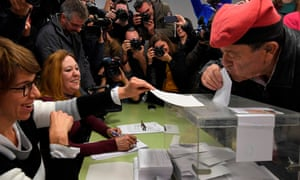 A man wearing an Catalan barretina hat kisses his ballot before casting his vote in Barcelona
