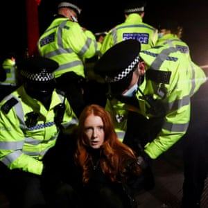 Police detain a woman as people gather at the memorial.