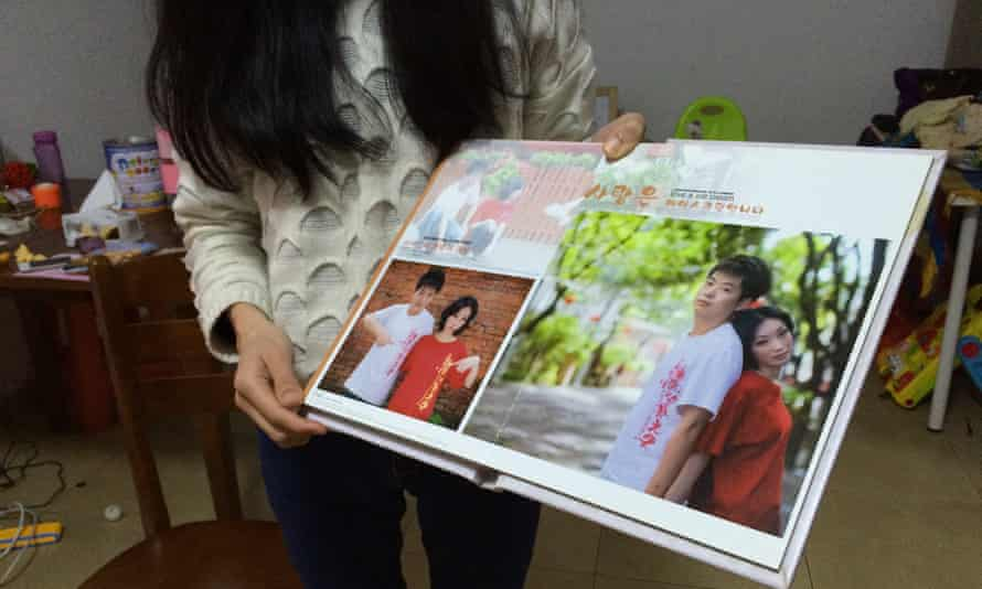 Yang Min holds up a photo album showing wedding photographs of her and her husband