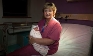 Midwife on a nightshift, Sue French, photographed at St Michael's Hospital, Bristol with a baby born 12 hours earlier.