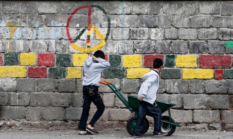 Young Turkish Kurds play in front of a wall painted the colours of the HDP in Diyarbakir.