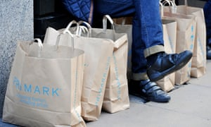 A Primark shopper surrounded by the chain's telltale brown paper bags.