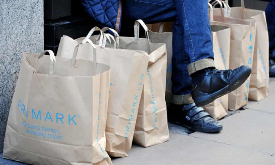 A shopper sits by Primark paper bags