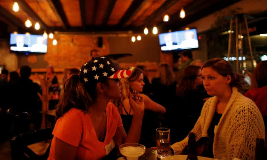 US Democrats living in Mexico chat as they watch a television broadcast of the third presidential debate at a restaurant in Mexico City.