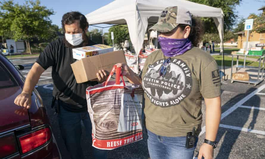 After last month's winter storm, many undocumented Texans turned to Catholic Charities for help. Alejandro DelValle, left, and Arlene Lozano help hand out supplies for a food drive in Austin sponsored by Catholic Charities.