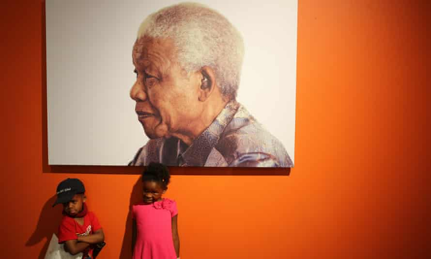 Two children pose in front of a portrait of Nelson Mandela at the Nelson Mandela Foundations Centre of Memory in Johannesburg.