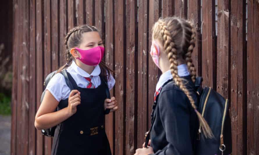 Two schoolgirls in uniform with rucksacks, wearing pink facemasks