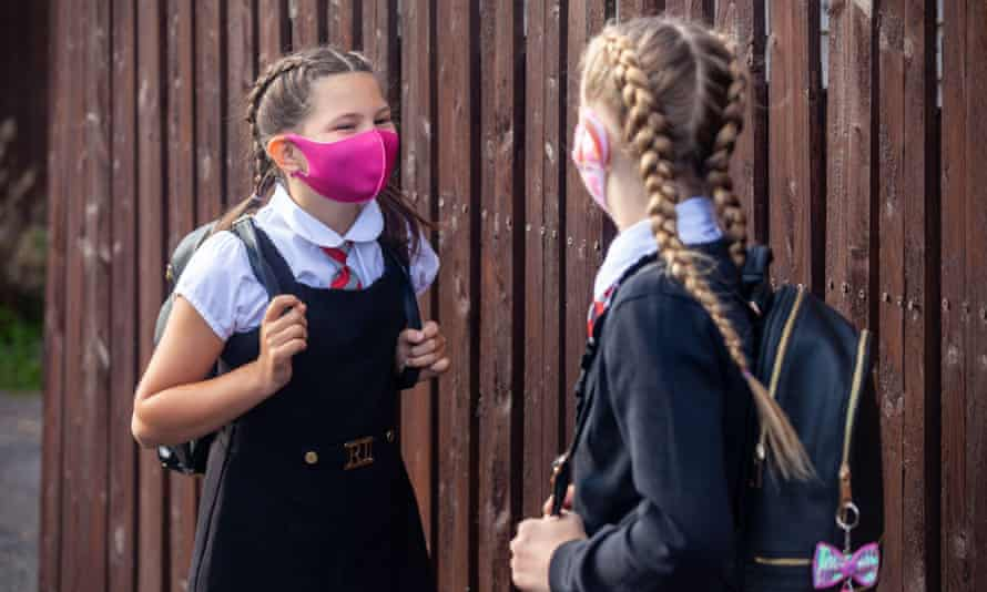 Two 10-year-old  girls chatting to each other and wearing face masks