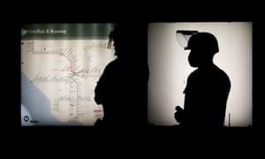 Police officers are silhouetted as they stand guard at a subway station during a protest in Los Angeles.