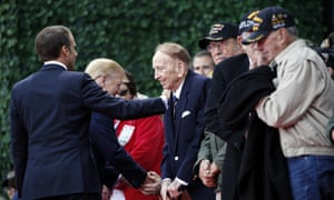 President Donald Trump and French President Emmanuel Macron greet veterans before the start of the service at the American cemetery at Colleville-sur-Mer