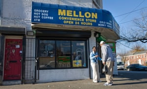 Convenience store owner Ephrame Kassay talks with a customer outside his ship in southeast Washington DC.