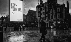 A sodden pedestrian passes an illuminated advertising sign in Hammersmith, London 2011