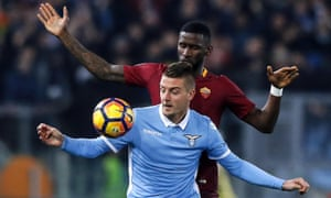 Lazio's Sergej Milinkovic-Savic, who scored their first goal, holds off Roma's Antonio Rüdiger, who was subject to concerted racist chanting by Lazio fans