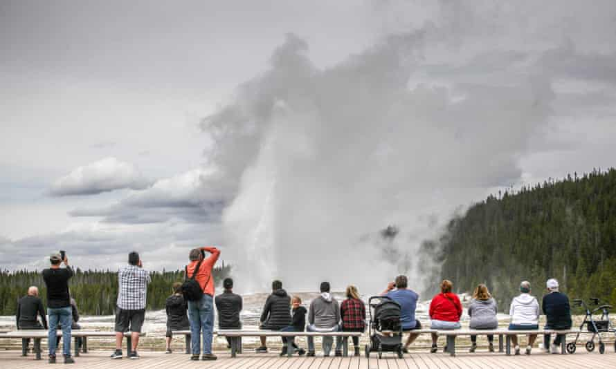 Visitors watch Old Faithful erupt after Yellowstone national park reopened on Monday.