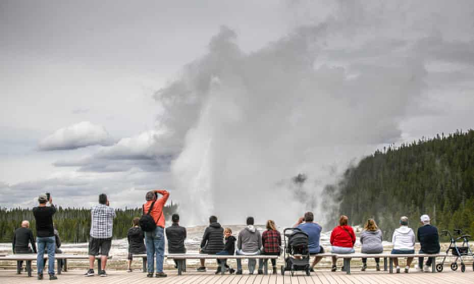 Visitors watch Old Faithful erupt on 18 May 2020, Yellowstone national park's opening day.