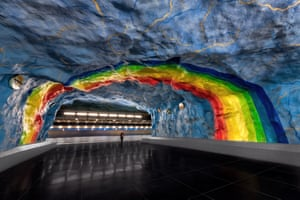 A painted rainbow arcs over a girl on the platform of Stadion metro station on the Stockholm T-Bana in Sweden.
