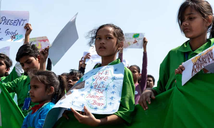 """Children carrying placards, one reading """"We are all in the same boat"""""""