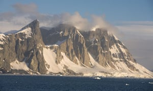 Unnamed peaks on the west coast of the Antarctic peninsula tower over the harsh Antarctic coast.
