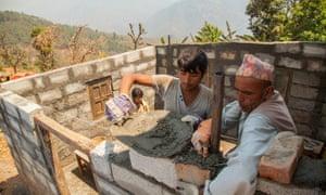Shopkeeper Gajendra Giri with family rebuilding his house