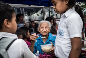 A grandmother feeds her grandchild at a charity kitchen run by volunteers and an NGO. Often, one person in the family ends up sacrificing their meal so that other family members can eat a bit more