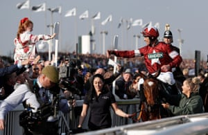 Davy Russell on Tiger Roll celebrates with a young spectator on the lead in after their victory