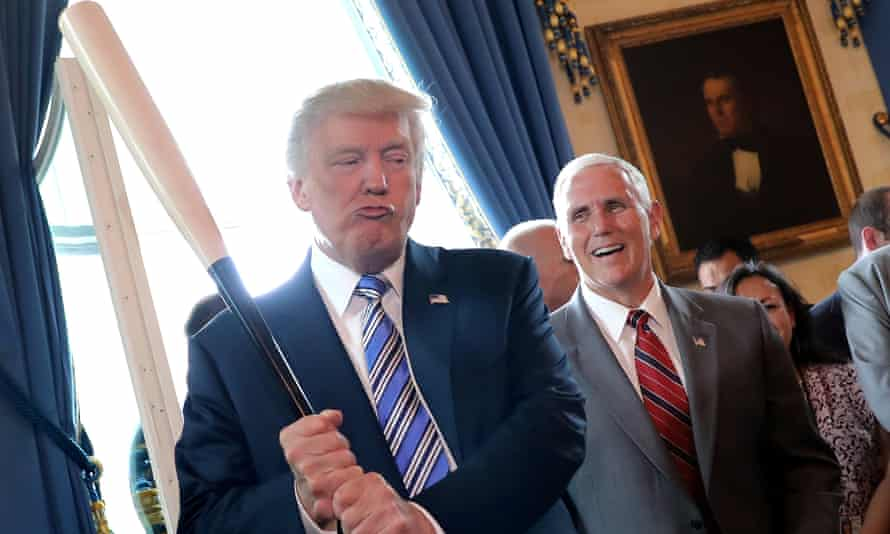 Vice-President Mike Pence laughs as Donald Trump holds a baseball bat at a Made in America product showcase event at the White House, in 2017.