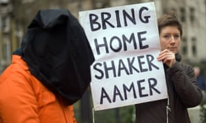 A protester holds a sign calling for the release of Shaker Aamer from Guantánamo Bay