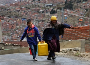 A woman and a child carry a bucket of water collected from a truck provided by officials of the Bolivian public water company in La Paz