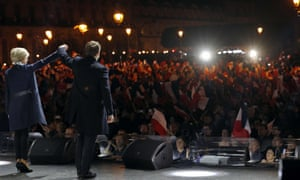 Emmanuel Macron stands with his wife Brigitte in front of supporters outside the Louvre.