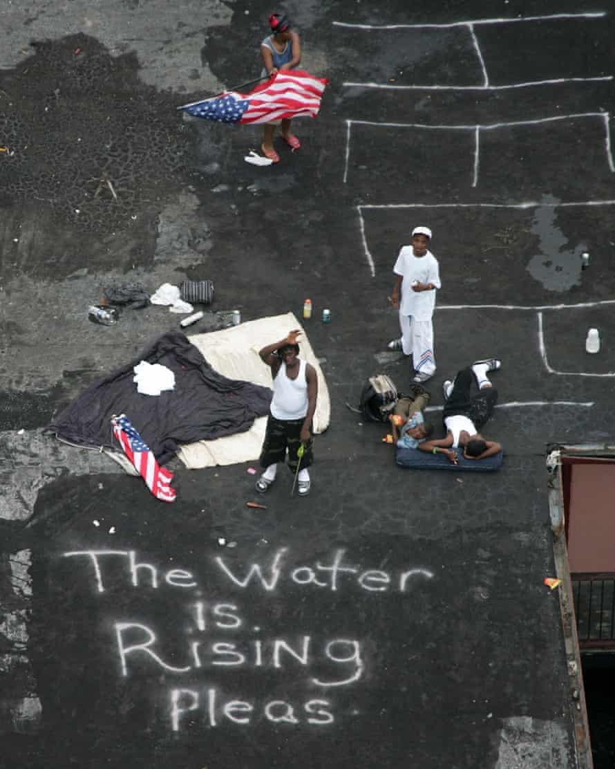 New Orleans residents wait on a rooftop to be rescued after Hurricane Katrina in 2005.