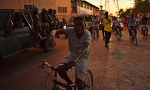 A boy rides a bike near a Senegalese Ecowas vehicle as they arrive at State House in Banjul.